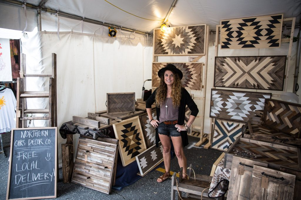 Northern Oaks Decor Company artisan stands in her Maker Marketplace tent with elaborately patterned oak panels.