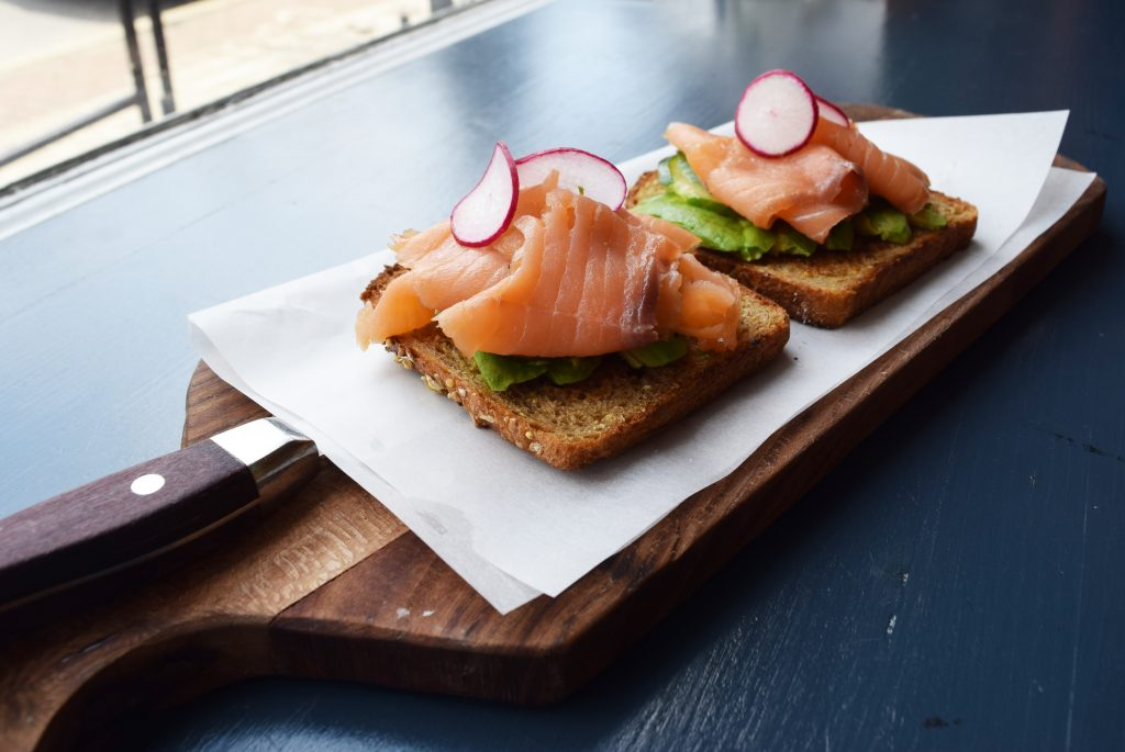 Chez Genese's toasted bread with avocado, salmon, and radish on wax paper atop a wooden cutting board.