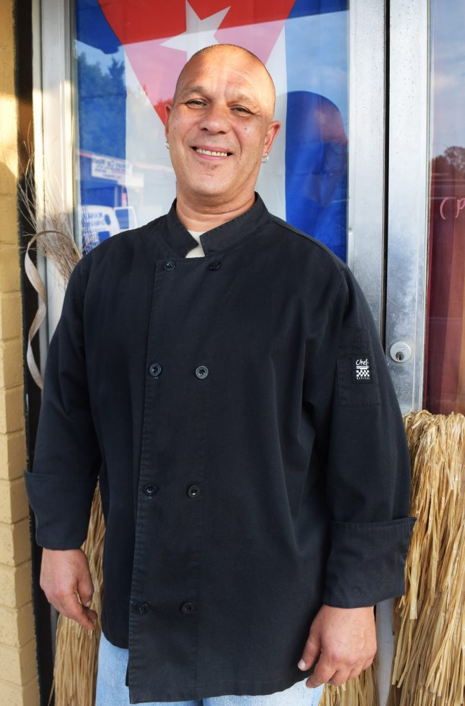 George Lopez stands in front of a Cuban flag in a black chefs coat.