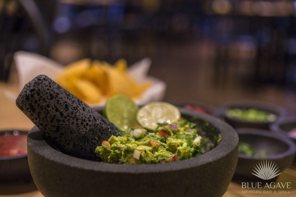 Blue Agave's guacamole presented with a lime garnish in a black stone mortar and pestle.