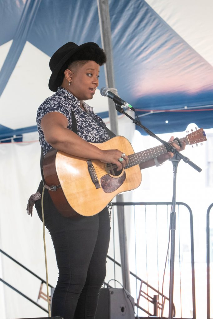 Amythyst Kiah stands in profile on stage, singing into a microphone and playing guitar.