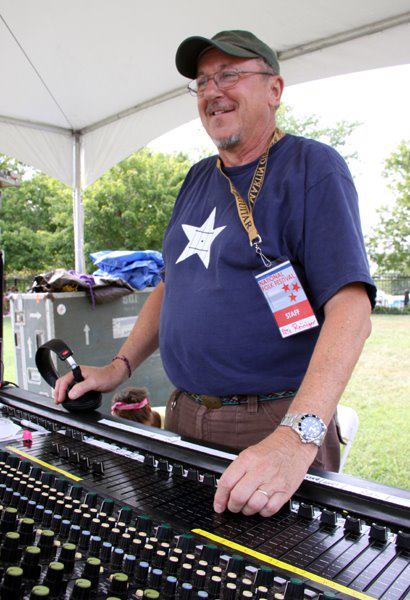 Peter Reiniger adjusts his sound board in a covered tent with a NC Folk Festival Staff lanyard around his neck.