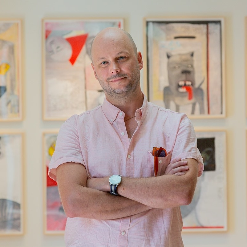 Brendan Greaves stands proudly with a slight smile and arms crossed in front of framed works of art on a gallery wall.