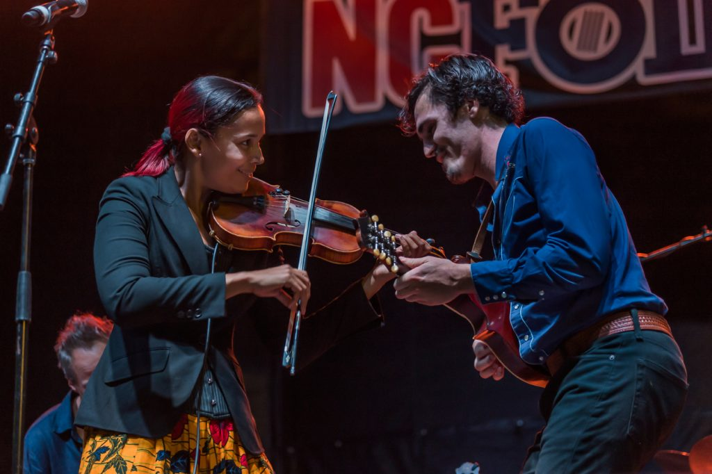 Rhiannon Giddens plays the fiddle as she smiles and leans towards to her fellow musician playing the guitar on a North Carolina Folk Festival stage.