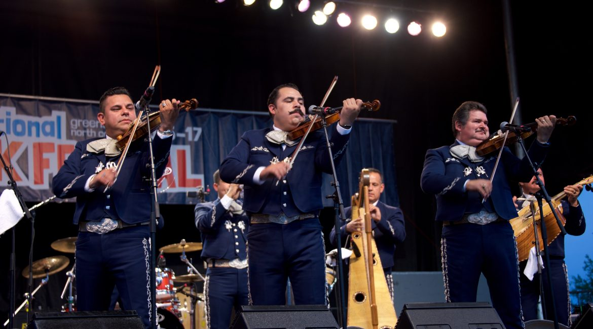 Three members of Mariachi Los Camperos preform on a festival stage in traditional mariachi attire.
