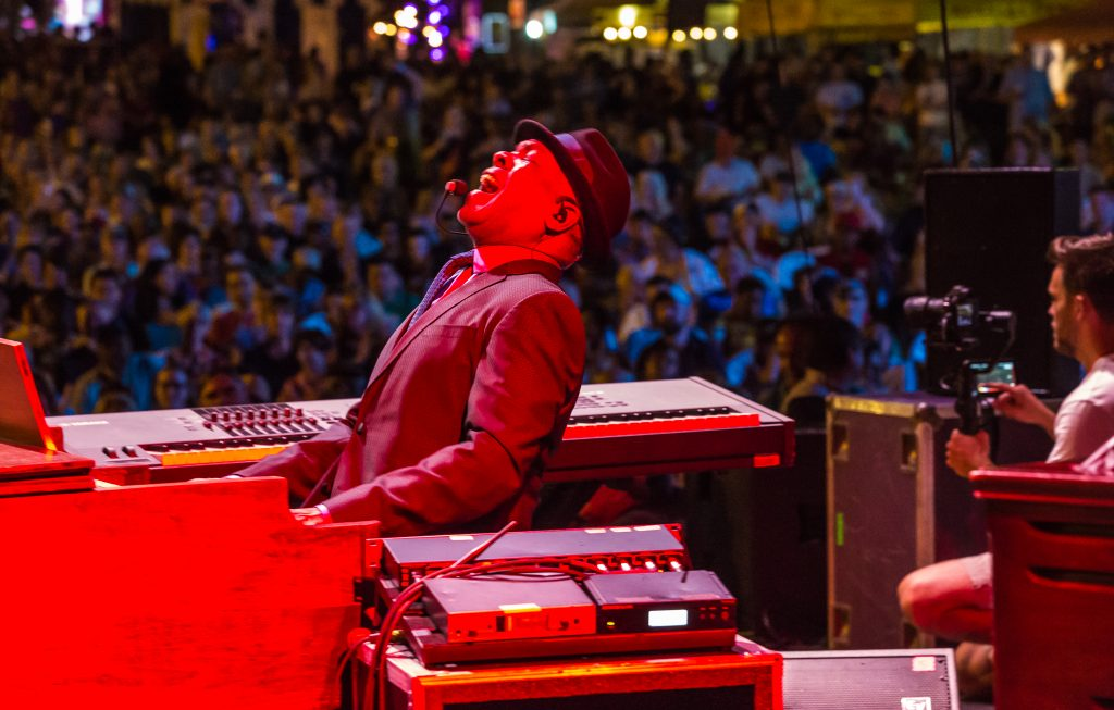 Musician bathed in red light leans back in delight as he plays piano on stage for a large crowd.