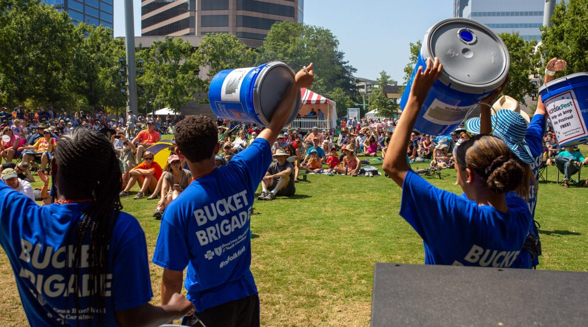 Bucket Brigade volunteers hold their blue donation buckets over their heads urging the crowd at LeBauer Park to contribute.