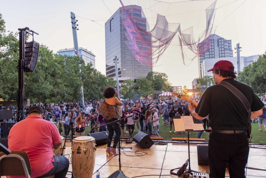 """Musicians preform at Towne Bank Stage at LeBauer Park. The crowd stands under an aerial textile sculpture, """"Where We Meet."""""""