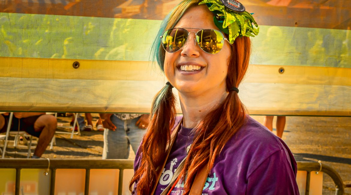 A volunteer wearing a NC Folk Fest shirt and flower hair ornament smiles at the camera.