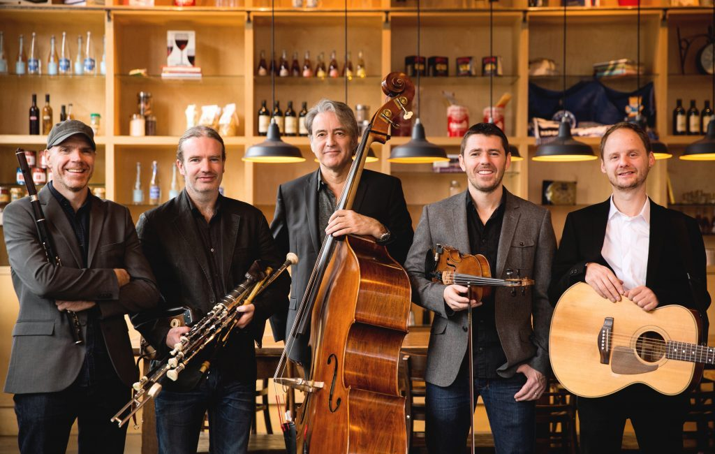 Lúnasa members with their instruments (a guitar, bass, bodhran, fiddle, and uilleann pipes) stand in front of a bar.
