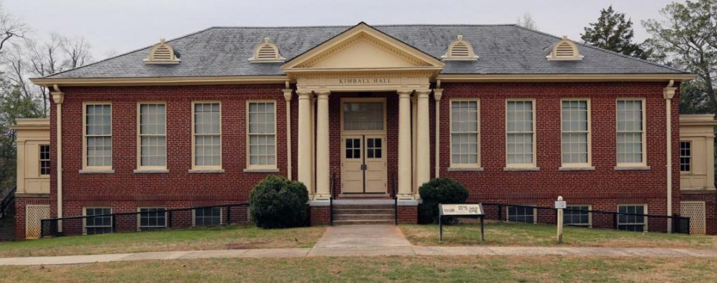 Red brick building and porch with a white wooden pediment and columns.
