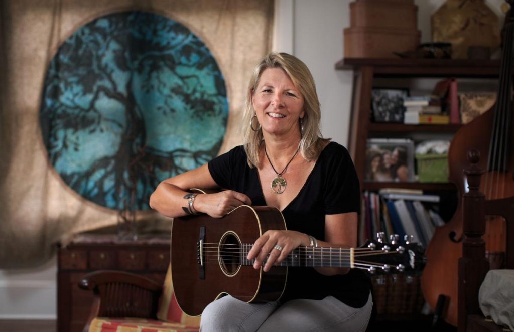 Laurelyn Dossett sits with her guitar in an interior space with a bass and circular tree wall decoration.