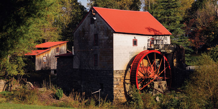 The mill has a red roof and a large red water wheel on the side.