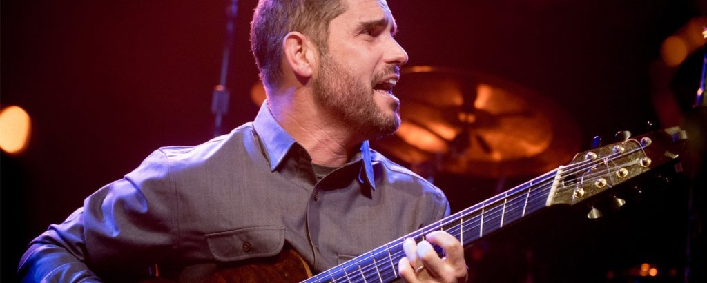 Charlie Hunter plays guitar on stage.