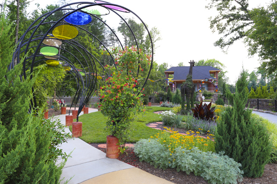 A sculpted walkway of metal and colored glass leads into the garden where there is a topiary giraffe.