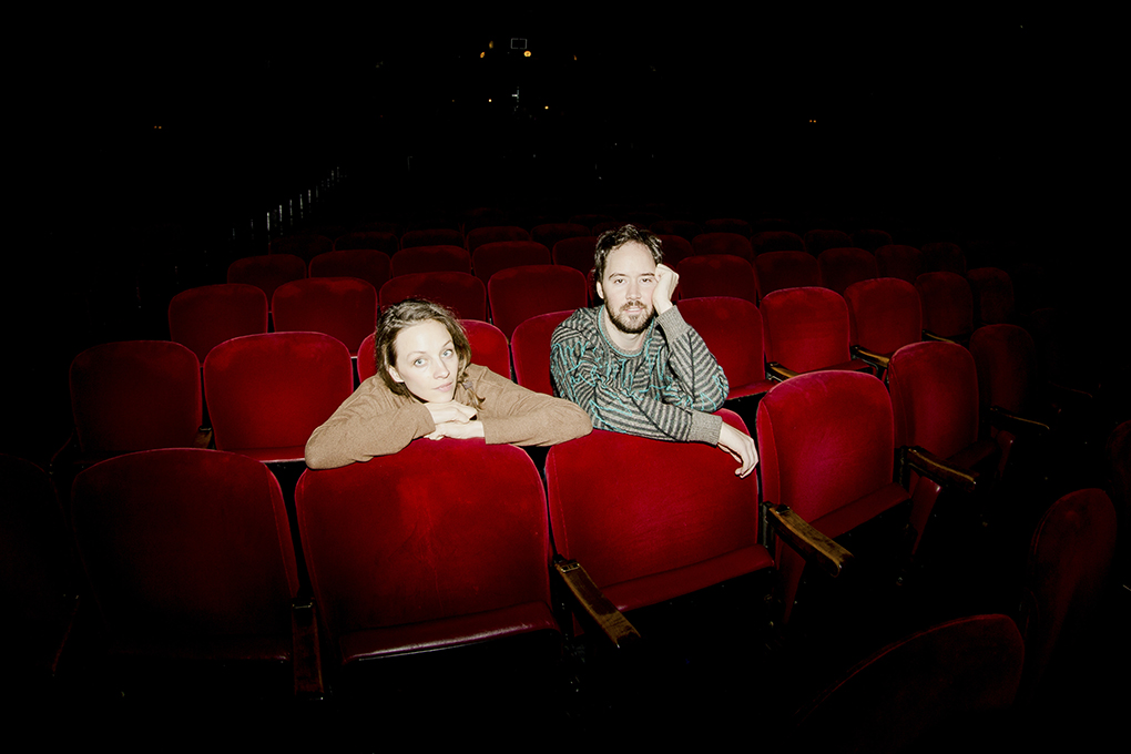 Emily and Andrew sit alone in a movie theater.
