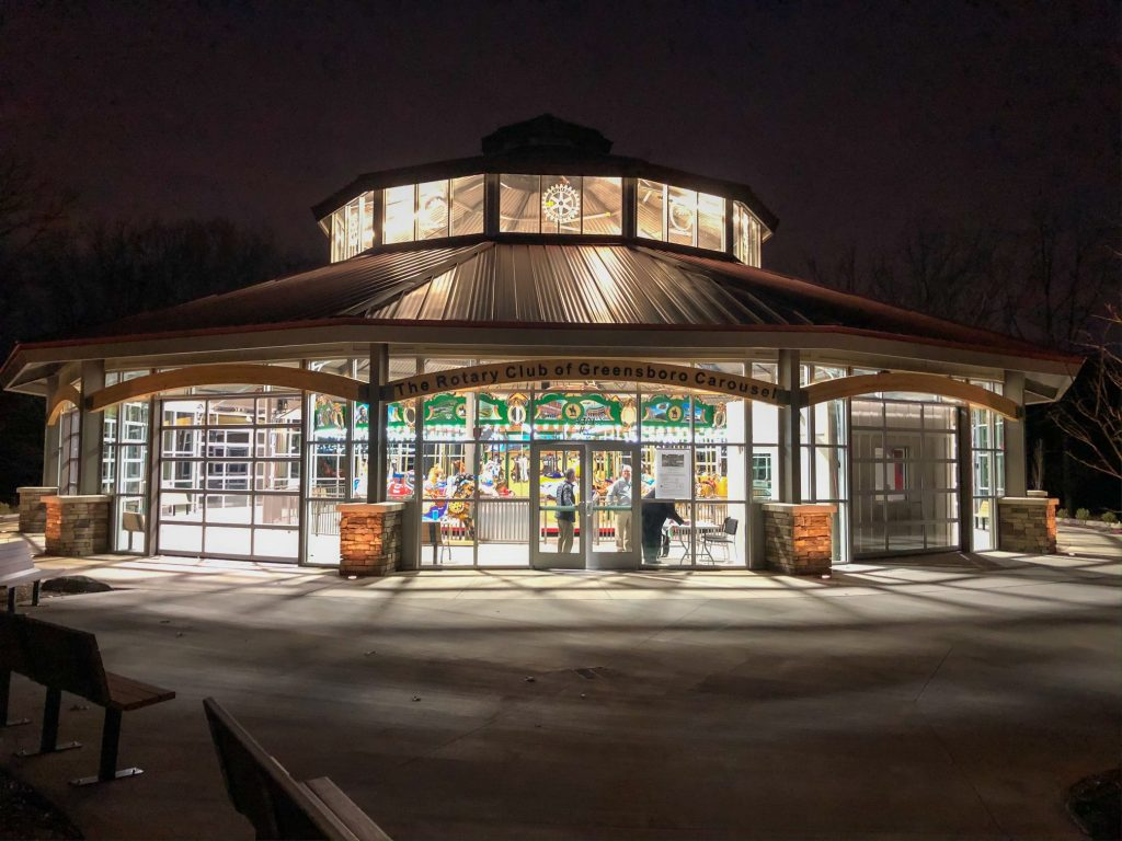 The carousel is enclosed by a large octagonal pavilion with floor-to-ceiling glass walls.