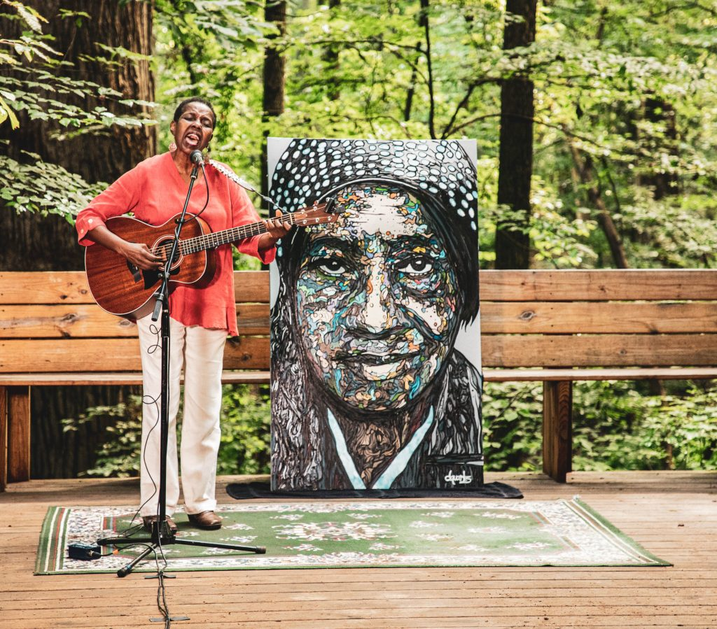 Jackson plays guitar on a deck in the forest. Behind her is a portrait of an African American woman.
