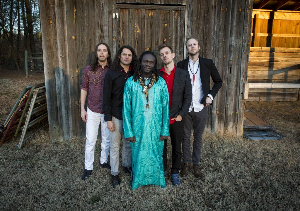 The five members of Diali Cissohko and Kaira Ba stand in front of a wooden barn. Diali wears traditional West African clothing.