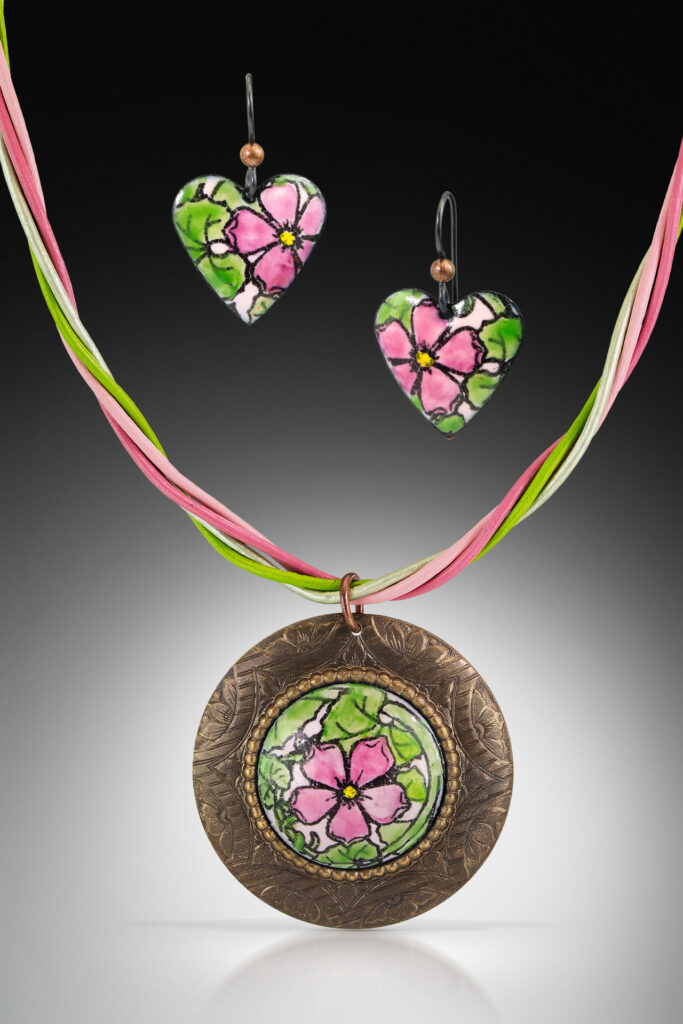 Neckless and earrings with pink flowers.