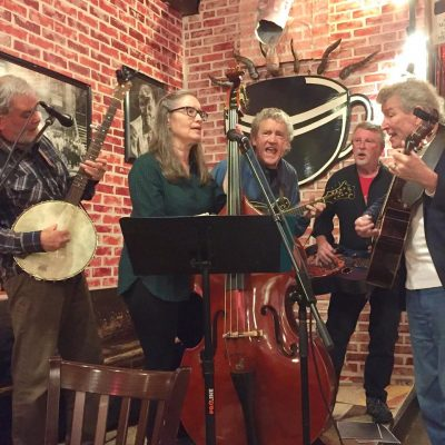 Five members of the Alley Rabbits perform banjo, bass, mandolin, and guitar in the corner of a brick building.